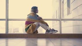 Den unga gulliga flickan sitter i bakgrunden av fönstren som hänsynsfullt ut ser fönstret lager videofilmer