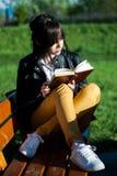 Den unga gulliga flickan sitter och läser en bok på härlig vårdag i parkera på en bänk royaltyfri bild