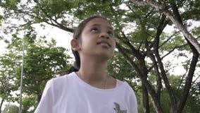 Den unga gulliga flickan som går på banan parkerar offentligt arkivfilmer