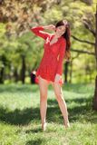 Den unga gulliga kvinnan i röd klänningdans i parkerar barfota Sk?nhetnaturplats med f?rgrik bakgrund, tr?d p? sommars?songen arkivbilder