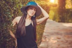Den unga gulliga kvinnan som poserar i en gräsplan, parkerar royaltyfria bilder