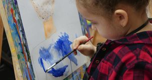 Den unga gulliga kvinnliga konstn?ren ?r i en konststudio som sitter bak en staffli och m?lar p? kanfas Dra process: i lager videofilmer