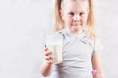 Den unga gulliga lilla blonda flickan i den vita t-skjortan som ler och rymmer exponeringsglas av, mjölkar Royaltyfri Fotografi