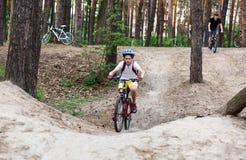 Den unga gulliga pojken i hjälm rider en cykel i parkerar Pojken går på vägen sport arkivbild