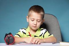 Den unga gulliga pojken som attraktioner med färgar, ritar Fotografering för Bildbyråer