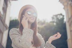 Den unga gulliga turisten talar på telefonen utanför och att bära hatten, royaltyfri foto