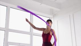 Den unga gymnastflickan gör övningar med bandet i ett repetitionrum stock video