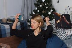 Den unga härliga affärskvinnan gör selfie på din telefon mot en vit vägg Royaltyfria Bilder