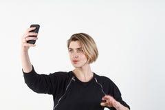 Den unga härliga affärskvinnan gör selfie på din telefon mot en vit vägg Royaltyfria Foton