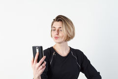 Den unga härliga affärskvinnan gör selfie på din telefon mot en vit vägg Fotografering för Bildbyråer