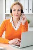 Den unga härliga affärskvinnan i hörlurar med mikrofon eller appelloperatör meddelar vid bärbar datordatoren Den orange tröjan är Arkivbild