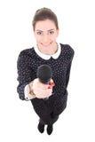 Den unga härliga affärskvinnan i svart klänning med mikrofonen är Arkivbilder