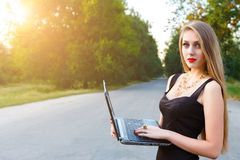 Den unga härliga affärskvinnan som rymmer en bärbar dator som arbetar i, parkerar arkivfoton