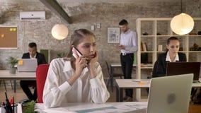 Den unga härliga affärskvinnan talar på telefonen i regeringsställning, folk knyter kontakt med teknologier, funktionsdugligt beg lager videofilmer