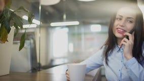 Den unga härliga arbetaren talar på mobil under hennes avbrott stock video