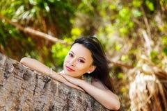 Den unga härliga asiatiska bruden under palmträdet på ett tropiskt är Arkivbild