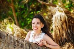 Den unga härliga asiatiska bruden under palmträdet på ett tropiskt är Arkivfoto