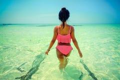 Den unga härliga asiatiska flickan i bikini tycker om sommarferier på den tropiska paradisstranden Sommarsemester och livsstilbeg Royaltyfria Bilder