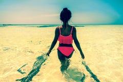 Den unga härliga asiatiska flickan i bikini tycker om sommarferier på den tropiska paradisstranden Sommarsemester och livsstilbeg Arkivfoto