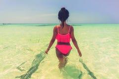 Den unga härliga asiatiska flickan i bikini tycker om sommarferier på den tropiska stranden Sommarsemester och livsstilbegrepp Royaltyfria Bilder