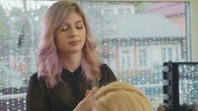 Den unga härliga barberareflickan tillfogar volymfrisyren till den nätta kvinnliga klienten arkivfilmer