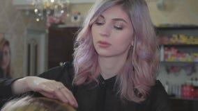 Den unga härliga barberareflickan tillfogar volymfrisyren till den nätta kvinnliga klienten lager videofilmer