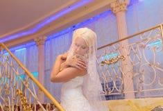 Den unga härliga blonda brudförtrogenståenden med stängt bära för ögon skyler Arkivfoton