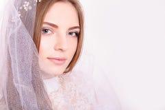 Den unga härliga blonda fästmöståenden med vitt veil/ Fotografering för Bildbyråer