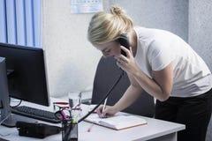 Den unga härliga blonda flickan arbetar i kontorsnärbilden Arkivbilder