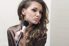 Den unga härliga flickan gör makeup fotografering för bildbyråer