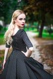 Den unga härliga blonda flickan med röd läppstift i hennes stora ljusa ögon och gör den i klänningen som poserar på gatorna, inst Arkivfoto