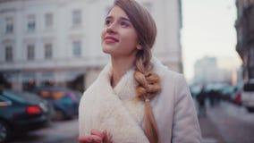 Den unga härliga blonda kvinnan smsar någon på hennes telefonstund som går ner gatan Hon verkar lycklig om vad