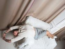 Den unga härliga blondinen ligger på soffan Raksträckan poserar Royaltyfri Foto