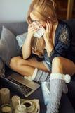 Den unga härliga blondinen på en soffa ser en bärbar dator och skrik arkivbilder