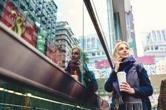 Den unga härliga blondinen reser vid arbete genom att använda smartphonen och den snabba radion 5G Arkivfoton