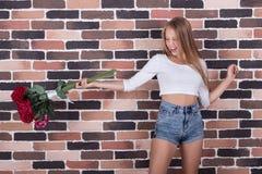 Den unga härliga blongflickan kastar rosor ut Fotografering för Bildbyråer