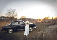 Den unga härliga bruden är därefter nära att svärta retro bilsolnedgångbakgrund Gifta sig med den gamla retro bilen för tappning  Royaltyfri Foto