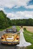 Den unga härliga bruden i ett trendigt snör åt klänningen med en bukett av blåa blommor i hennes händer som poserar nära cabriole royaltyfri bild