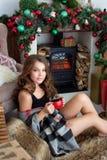 Den unga härliga brunetten på julhelgdagsafton sitter nära en spis, och drinkte från ett rött rånar Arkivbilder