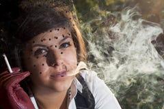 Den unga härliga brunetten röker en cigarett i panelljus Royaltyfri Fotografi