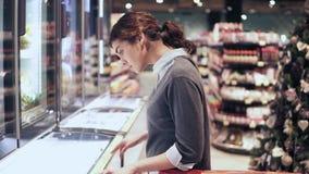 Den unga härliga brunettflickan kommer upp till en frys som försöker att avgöra vilken produkt som köper att se prislappen shoppi arkivfilmer