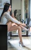 Den unga härliga brunettkvinnan i vit snör åt den långa muffblusen som applicerar rosa färgpolermedel på henne, spikar tår Förför Royaltyfri Fotografi