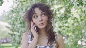 Den unga härliga brunettkvinnan talar på telefonen i parkera lager videofilmer