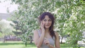 Den unga härliga brunettkvinnan talar på telefonen i parkera stock video