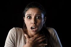 Den unga härliga förskräckta spanska kvinnan i chock och överraskningen vänder mot uttryck som isoleras på svart Royaltyfria Foton