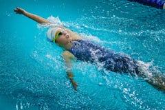 Den unga härliga flickaidrottsman nen simmar ryggsim Arkivfoto
