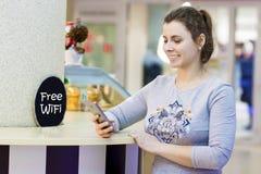 Den unga härliga flickan använder smartphonen i fri zon för Wi Fi i shoppinggalleriakafé Attraktiv kvinnaWifi zon Fritt begrepp w royaltyfri fotografi
