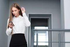 Den unga härliga flickan använder smartphonen i regeringsställning med glasväggar Arkivbild