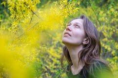 Den unga härliga flickan bland gulingen blommar på buskarna på ljus solig dag Arkivbild