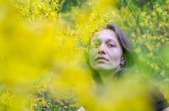 Den unga härliga flickan bland gulingen blommar på buskarna på ljus solig dag Fotografering för Bildbyråer